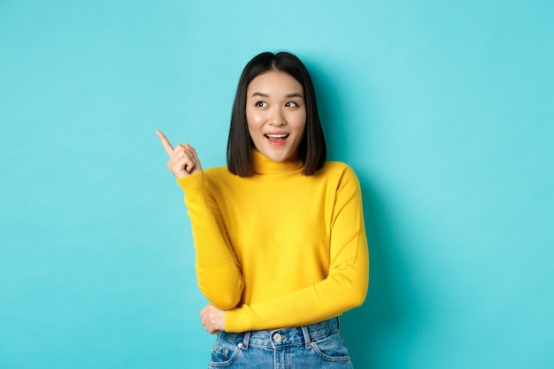ショッピングのコンセプト。黄色いセーターの魅力的な韓国の女の子の肖像画、コピースペースでプロモーションのオファーを示し、喜んで笑顔、青い背景で左を指して見て