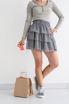 ショッピングのコンセプト。リサイクル。クレジットカードを持っている女性、近くの環境に優しい紙の買い物袋。モックアップ