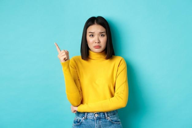 쇼핑 개념. 노란색 스웨터 가리키는 손가락 왼쪽, 인상을 찌푸리고 파란색 위에 서있는 복사 공간에 나쁜 소식을 보여주는 슬프고 우울한 아시아 소녀.