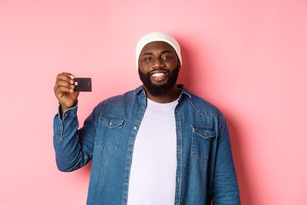 ショッピングのコンセプト。クレジットカードを示して、満足して微笑んで、購入して、ピンクの背景の上に立っているビーニーの満足している若いひげを生やした男。
