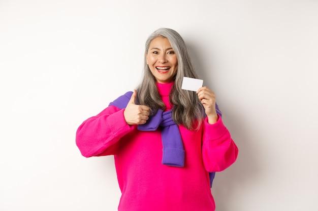 ショッピングのコンセプト。プラスチック製のクレジットカードと親指を立てて、銀行の昇進、白い背景をお勧めします。