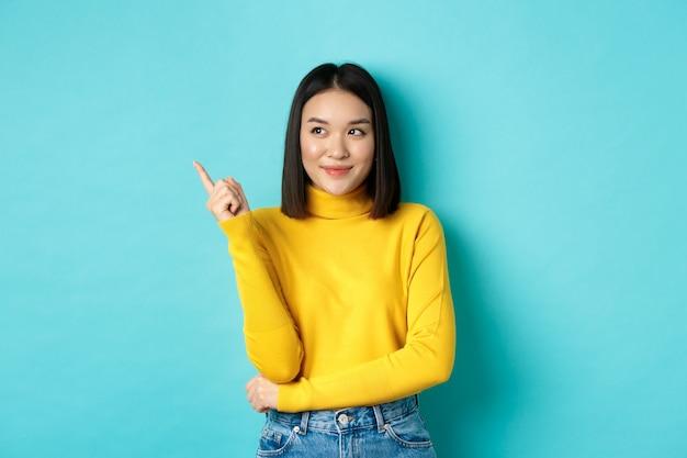 쇼핑 개념. 파란색 위에 서있는 만족스러운 얼굴로 광고를 보여주는 노란색 스웨터에 세련된 아시아 여성 모델, 미소하고 왼쪽 손가락을 가리키는.