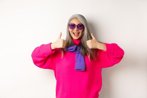 쇼핑 개념. 세련 된 아시아 수석 여자 선글라스와 트렌디 한 옷, 승인에 엄지 손가락을 보여주는 흰색에 서있는 상점 추천.