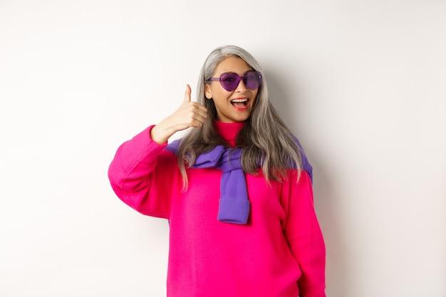 Concetto di acquisto. elegante donna anziana asiatica in occhiali da sole e abbigliamento alla moda, mostrando il pollice in su in segno di approvazione, consigliando il negozio, in piedi su sfondo bianco