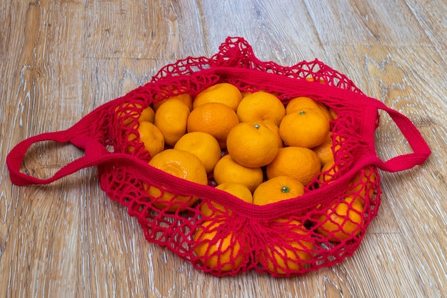 Shopping concept. traditional fruit in russia for new year and christmas. tangerines lying in a red shopping bag on a wooden, top view, close-up. healthy food concept
