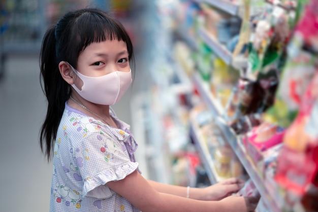 바이러스 발생 중 아시아 아이들과 쇼핑 개념. 코로나 바이러스 전염병에 슈퍼마켓에서 과일을 구입하는 얼굴 마스크를 착용하는 아이.