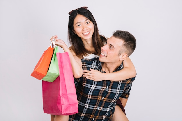 Shopping concept with man carrying girlfriend