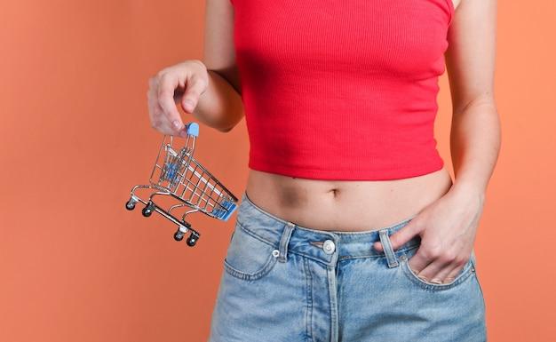 Концепция покупок. женщина, держащая мини-корзину на оранжевом