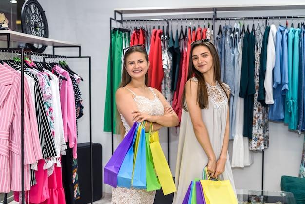 ショッピングのコンセプト。笑顔の大きなモールで買い物袋を持つ若い女性