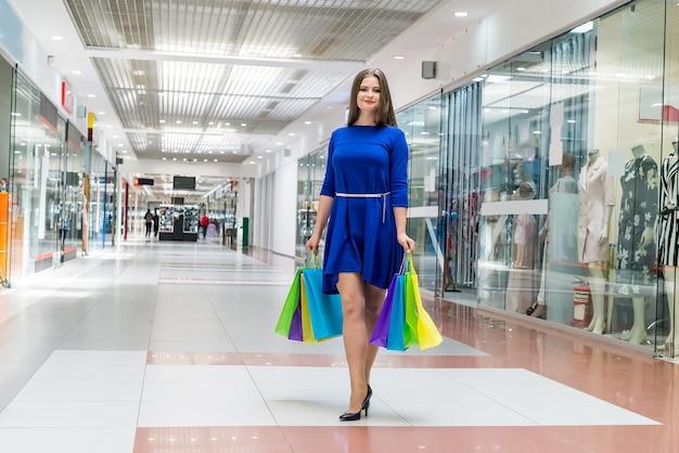 ショッピングの概念、ショッピングモールでバッグを持つ女性