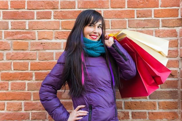 쇼핑, 소비자 및 판매 개념-도시 거리에 벽돌 벽 배경 위에 많은 쇼핑백을 들고 아름 다운 여자