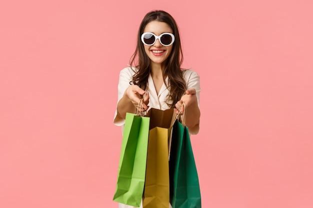 쇼핑, 소비자 개념. 쾌활한 매력적인 갈색 머리 소녀, 쇼핑백을 들고 웃 고, 안경을 쓰고, 상점 노점을 통해 탐색을 즐기고, 분홍색 즐거운 서