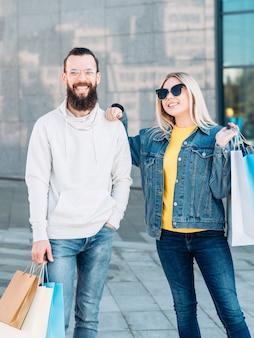 ショッピングカップル都市の消費主義市内中心部で紙袋を持つ若い男性と女性の笑顔