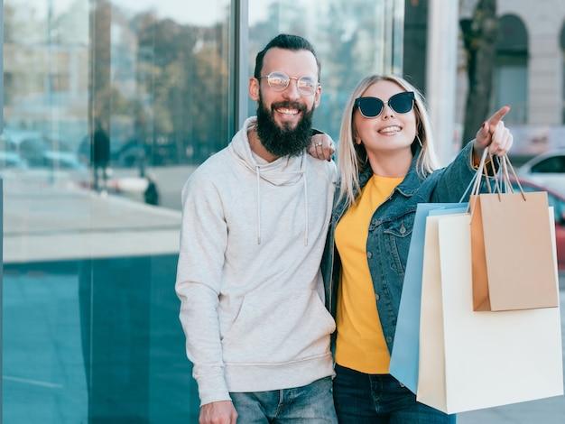 ショッピングカップル都市の消費主義仮想オブジェクトを指す紙袋で若い男性と女性を笑顔