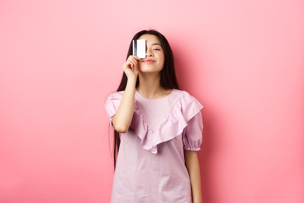 Shopping. cute candid woman smiling, showing plastic credit card on face, standing in dress against pink background.
