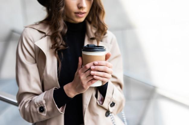 Giornata di shopping. pausa caffè. attraente giovane donna con sacchetti di carta che cammina sulla strada cittadina.