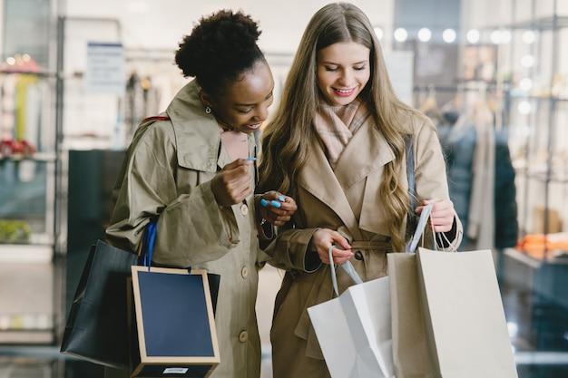 買い物の日。国際的なガールフレンド。ショッピングモールの女性。