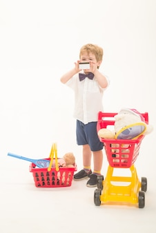 Shopping discount sale concept boy with credit card happy little boy with shopping cart and basket