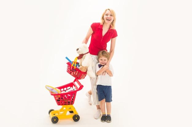 Покупки, скидки, концепция продажи. мать с сыном по магазинам. счастливый маленький мальчик с матерью в магазине. малыш играет в магазине. мальчик за покупками. маленький ребенок с пластиковой тележкой для покупок.
