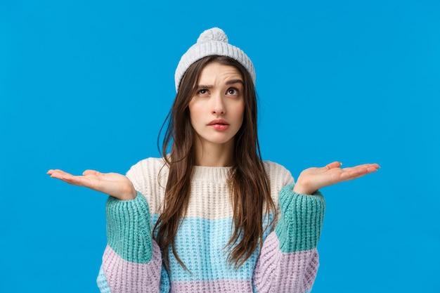 ショッピング、割引、広告のコンセプト。クリスマス休暇の贈り物を探している、腰を上げて優柔不断で思慮深い若い女性、手に何かを持って手のひらを上げる、2つのバリエーション、選択をする