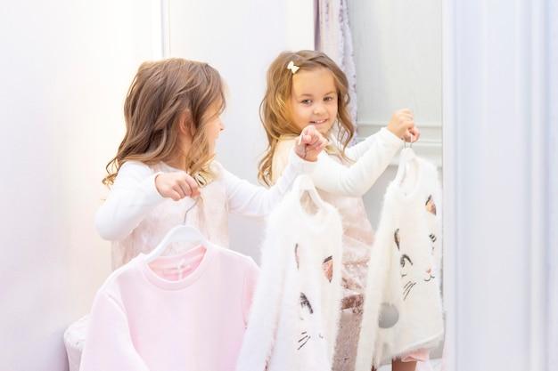 쇼핑. 할인. 작은 소녀 shopaholic. 부티크 피팅 룸에서 부드럽게 핑크색으로 아름다운 드레스를 시도하는 소녀. 쇼핑 센터, 쇼핑. 감정