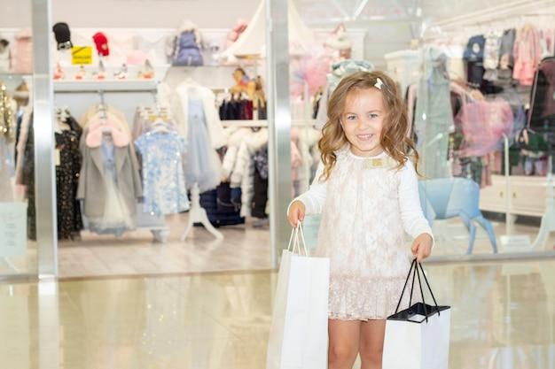 Shopping. discounts. little girl shopaholic. girl with shopping bags in hands. white bags copyspace. shopping center, shopping. emotions
