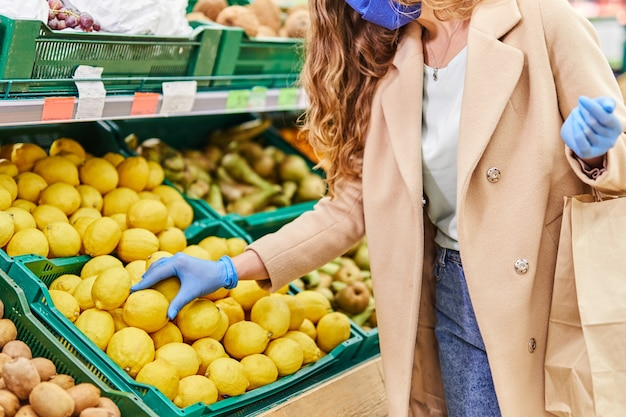Покупки во время пандемии covid-19. женщина в маске и перчатках покупает цитрусовые на рынке.
