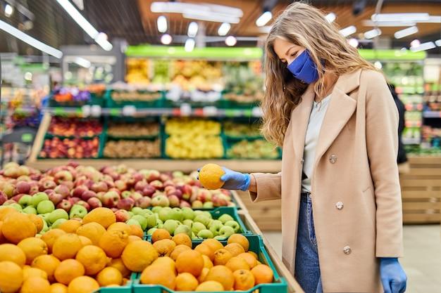 コロナウイルスcovid-19パンデミック時の買い物。顔のマスクの女性は市場で柑橘系の果物を購入します。