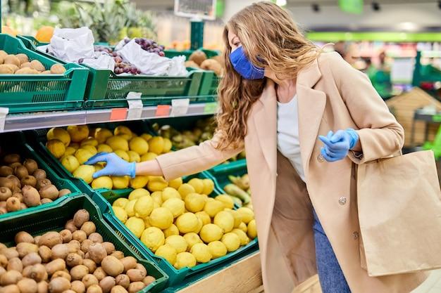 パンデミック時の買い物。顔のマスクとゴム手袋の女性は、市場で柑橘系の果物を購入します。