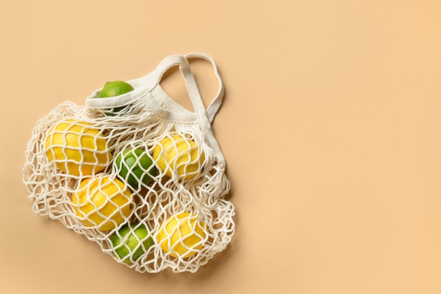 Shopping eco mesh bag with friuts, lemon, lime, banana on beige. zero waste. view from above.