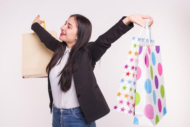 ショッピング、感情、人々の概念-買い物後のカラフルな紙袋を持つ若い幸せなアジアの女性
