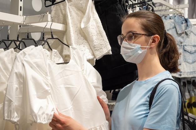 Covid19 동안 쇼핑, 패션, 스타일, 사람들 - 코로나바이러스로부터 자신을 보호하기 위해 의료용 마스크를 쓴 아름다운 소녀가 가게에서 옷을 선택하고 있습니다. 뉴노멀 컨셉.