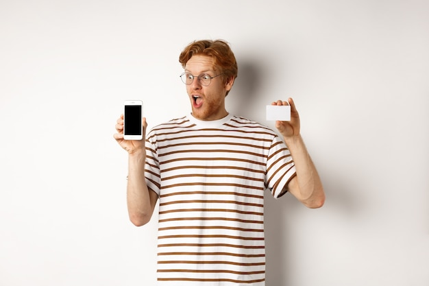 Shopping and finance concept. amazed young man with red hair showing plastic credit card and smartphone blank screen, staring at display impressed, white background.