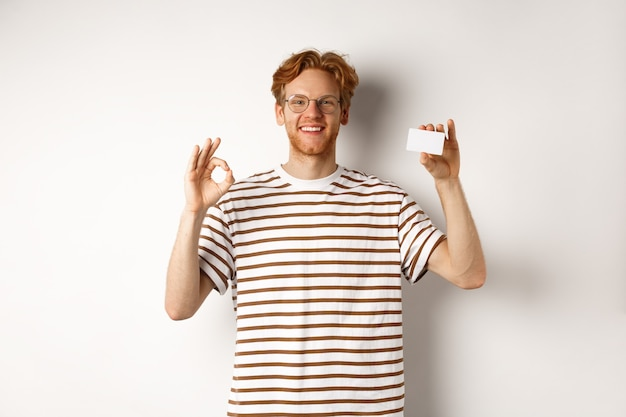Shopping and finance concept. satisfied male bank client showing ok sign and plastic credit card, smiling happy at camera.