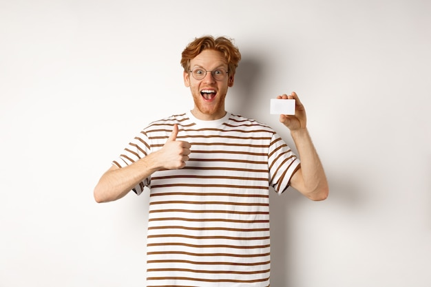 Shopping and finance concept. satisfied male bank client showing thumbs-up and plastic credit card, smiling happy at camera.