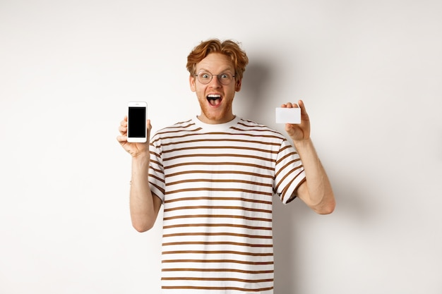 Shopping and finance concept. young man showing blank mobile screen and plastic credit card, smiling at camera, white background.