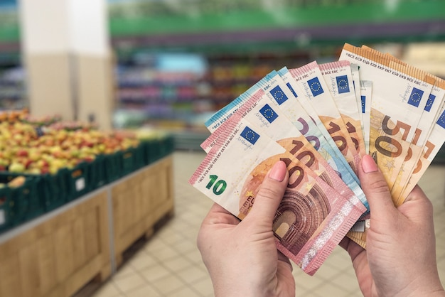 Shopping in fruit store, female hands with euro, closeup