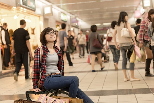 Shopping girl of asian sit on chair and take rest on street in taipei, taiwan.