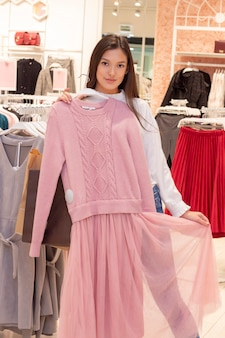 Shopping girl. a beautiful girl with long dark hair is in a clothing boutique, chooses a dress for herself. puts a dress on herself. vertical photo. in the hands of a bag