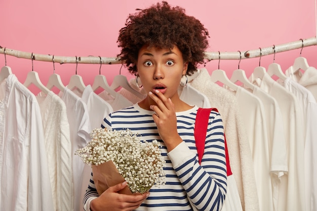 Shopping girl gasps from great wonder, keeps mouth opened, stands against white clothes, holds bouquet, shocked to forget wallet at home, isolated over pink background