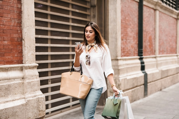 Shopping girl looking at her mobile phone