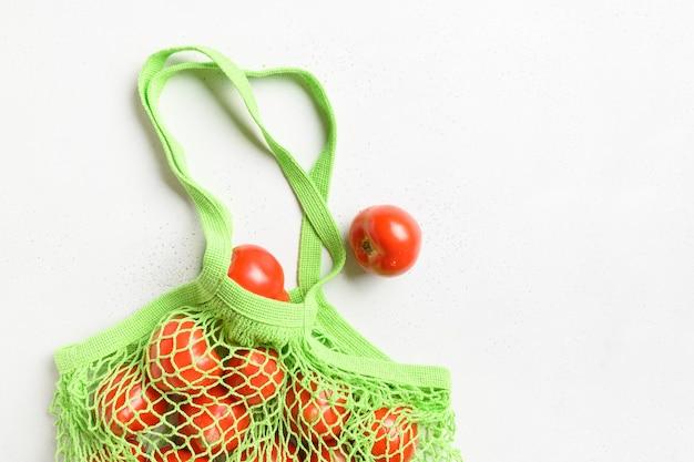 Зеленая сетка для покупок с помидорами на белом столе. нулевые отходы. вид сверху.