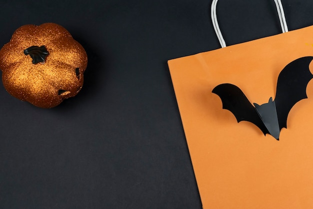 Shopping halloween flat lay. layout with copy space. pumpkin about lantern, orange shopping bag and bat on a black background.