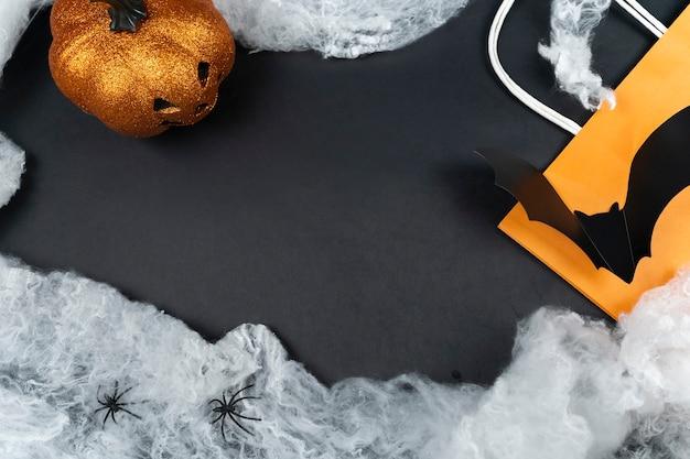 ショッピングハロウィンフラットレイ。コピースペースのあるレイアウト。ランタンについてのカボチャ、オレンジ色の買い物袋、黒い背景に蜘蛛の巣とコウモリ。