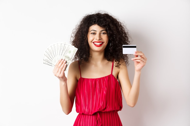 ショッピング。プラスチックのクレジットカードとドルの鰓、笑顔でカメラを見て、赤いドレス、白い背景を身に着けている幸せな美しい女性。
