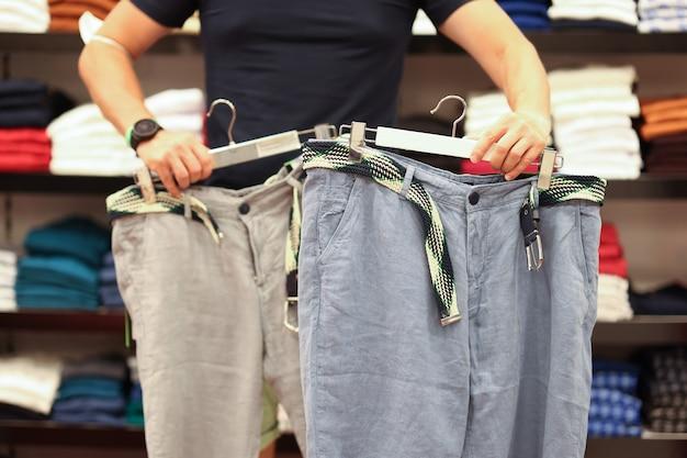 男性の衣料品店でのショッピング男性は衣料品店のショッピングコンセプトで服を選ぶ
