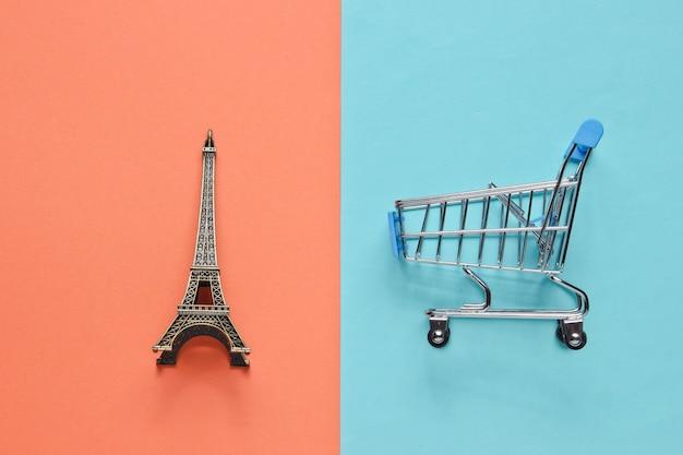パリのミニマルなコンセプトでのショッピング。ショッピングカート、パステルカラーの背景にエッフェル塔の置物。上面図