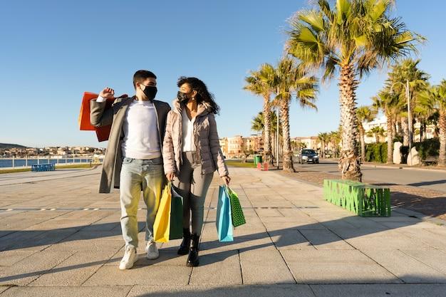 코로나 바이러스 대유행 젊은 부부가 검은 보호 마스크를 쓰고 서로 눈을 들여다보고있는 오늘날의 도시에서 쇼핑