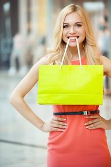 ショッピングは楽しいです。彼女の口に買い物袋を持って笑顔の美しい若い女性 Premium写真
