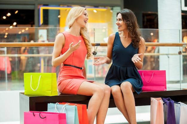 Покупки это весело. две красивые молодые женщины с хозяйственными сумками в торговом центре